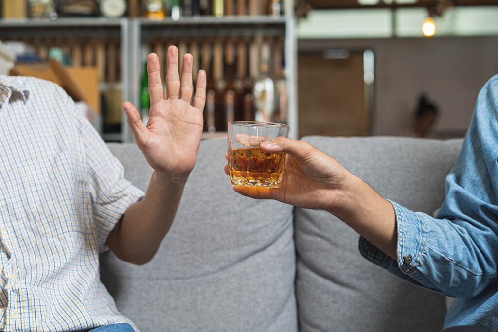 One hand offers an alcoholic beverage to another who holds a hand up to refuse it